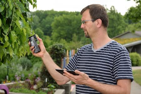 A user testing a plant leaf with the MultispeQ