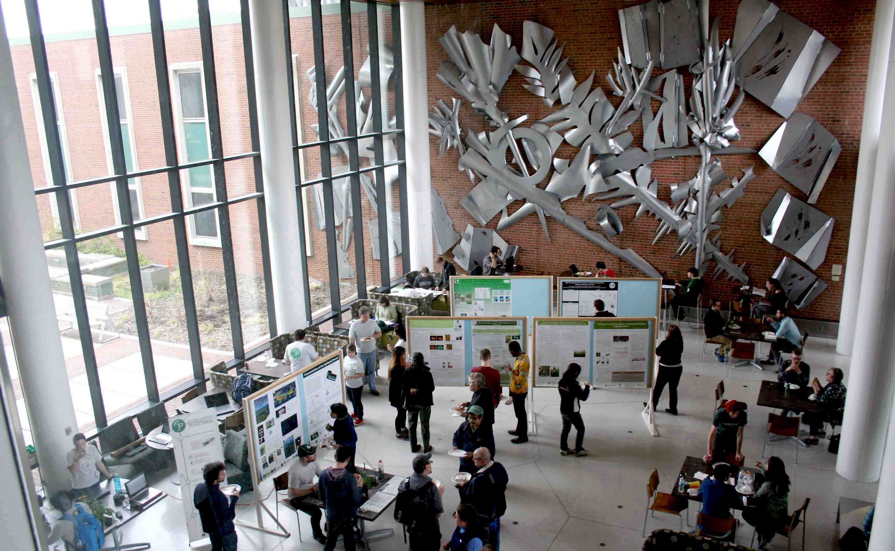 Image of attendees roaming the floor during lunch time, checking out posters and device demos.